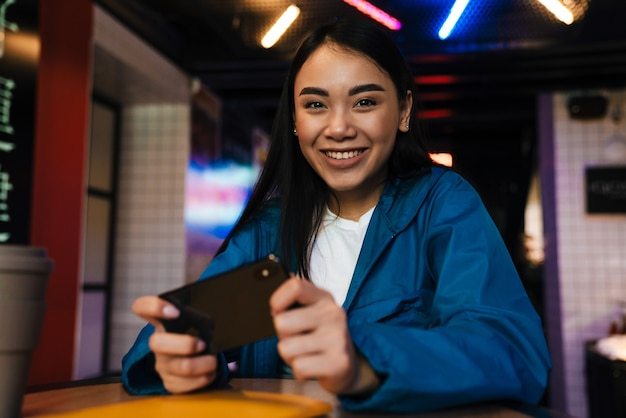 Podekscytowana azjatycka kobieta grająca w grę wideo na telefonie komórkowym siedząc w kawiarni