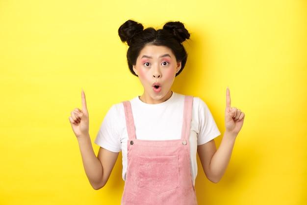 Podekscytowana azjatycka modelka z makijażem glamour, wskazująca palcami w górę i zdziwiona, sprawdzająca ofertę promocyjną, stojąca na żółtym tle