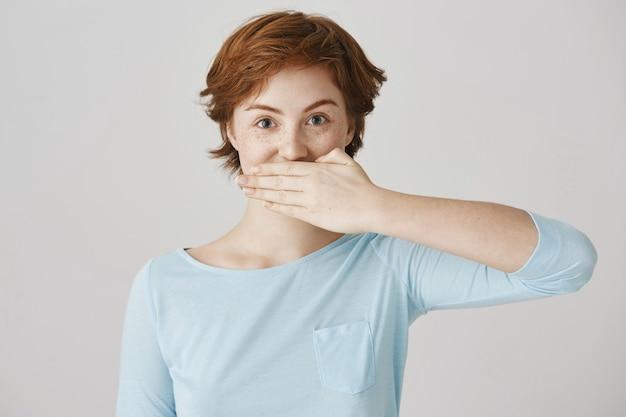Podekscytowana bezczelna ruda dziewczyna pozuje przy białej ścianie