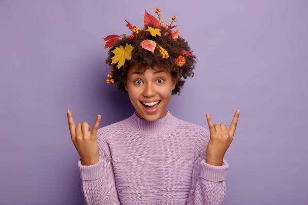 Podekscytowana beztroska kobieta afro bawi się na jesiennej imprezie, wykonuje rock n rollowy gest, heavy metalowy znak, ma kręconą fryzurę z jesiennymi liśćmi, czuje się pobudzona, nosi fioletowy swobodny sweter.
