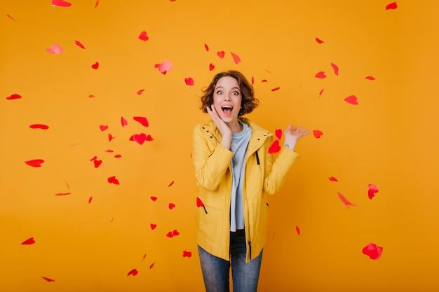 Podekscytowana biała dziewczyna z jasnobrązowymi falującymi włosami pozuje w walentynki. kryty zdjęcie szczęśliwej młodej kobiety stojącej pod upadłymi sercami i śmiejąc się.
