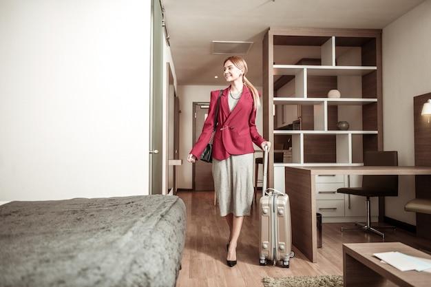 Podekscytowana bizneswoman. rozpromieniona piękna bizneswoman czuje się podekscytowana przybyciem do hotelu z bagażem