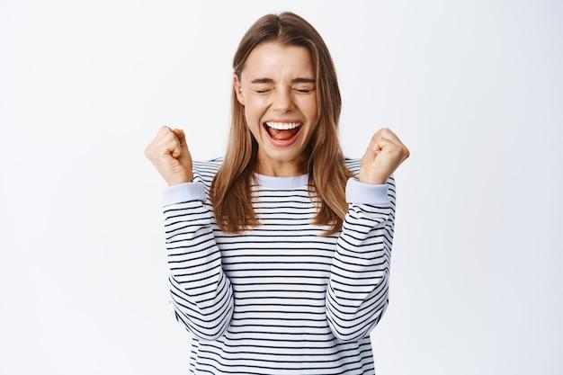 Podekscytowana blond dziewczyna krzycząca z radości, skacząca ze szczęścia i świętująca zwycięstwo, uśmiechnięta zdumiona, triumfująca z sukcesu, biała ściana