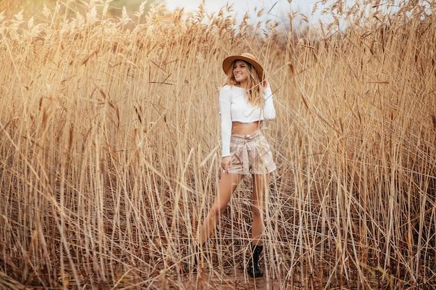 Podekscytowana blond szczęśliwa dziewczyna w stylu safari w słomkowym kapeluszu chodzi po naturze wśród trzcin.