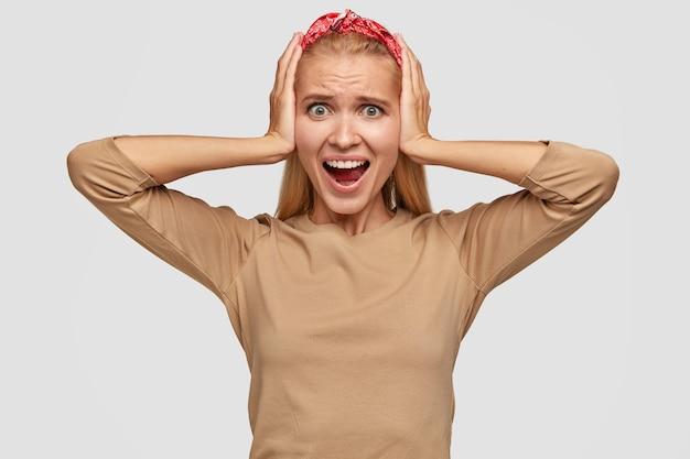 Podekscytowana blondynka młoda kobieta pozuje przy białej ścianie