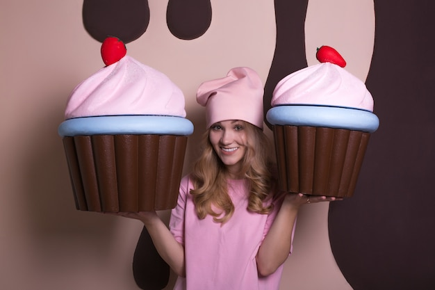 Podekscytowana blondynka w różowej czapce, ciesząca się dużymi babeczkami w studio