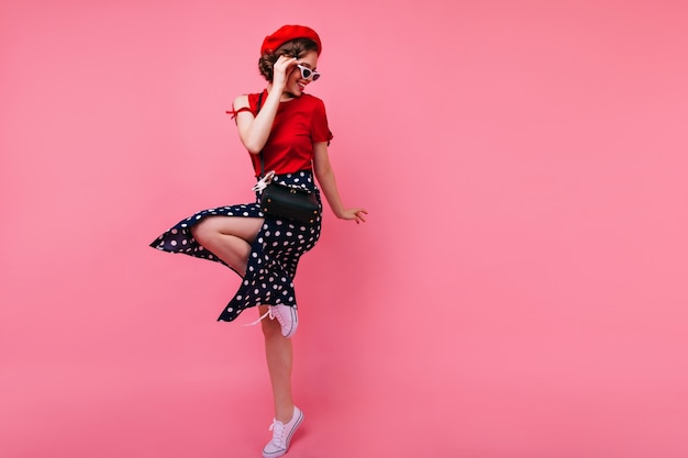 Podekscytowana brunetka dama w czarnej spódnicy tańczy na różowej ścianie. atrakcyjna biała dziewczyna we francuskim berecie.