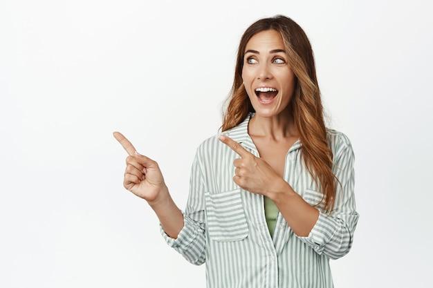 Podekscytowana brunetka dysząca zdumiona, wskazując palcami w lewo