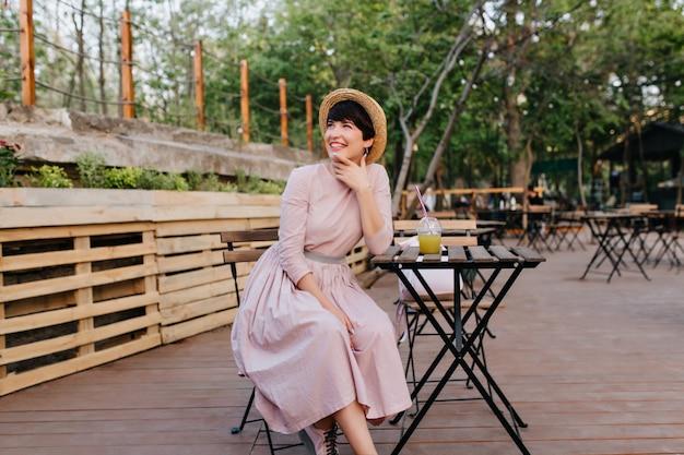 Podekscytowana brunetka dziewczyna w pięknej staromodnej sukni dotykając twarzy z czarującym uśmiechem odpoczywa w kawiarni na świeżym powietrzu