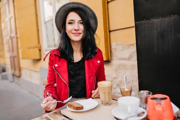 Podekscytowana brunetka kobieta w kapeluszu odpoczywa w kawiarni