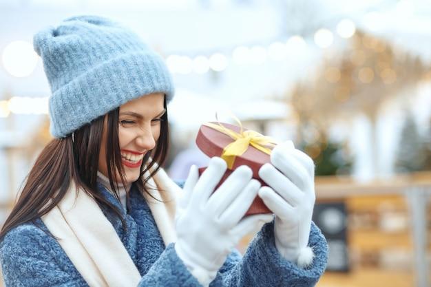Podekscytowana brunetka kobieta w płaszczu zimowym trzymająca pudełko na targach bożonarodzeniowych. miejsce na tekst