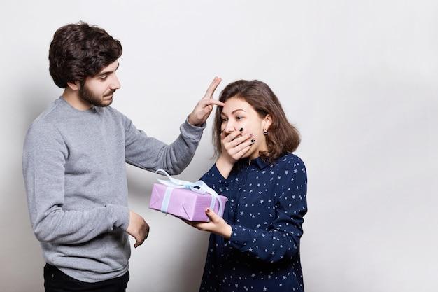 Podekscytowana brunetka trzyma prezent w dłoniach i jest zaskoczona jego otrzymaniem. ostrożny hipster daje prezent swojej dziewczynie i delikatnie wygładza włosy. uśmiechnięta para z teraźniejszością