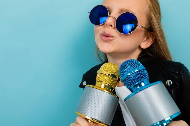 Podekscytowana charyzmatyczna dziewczyna śpiewa w karaoke z dwoma mikrofonami na powierzchni niebieskiej ściany