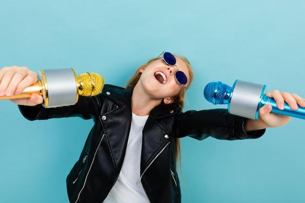 Podekscytowana charyzmatyczna dziewczyna śpiewa w karaoke z dwoma mikrofonami na tle niebieskiej ściany