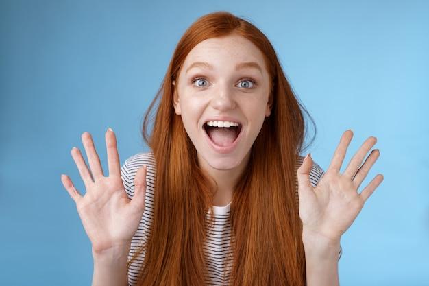 Podekscytowana charyzmatyczna szczęśliwa żywa ruda młoda zabawna kobieta uśmiechnięta zachwycona otwartymi ustami zafascynowana szeroko otwartymi oczami zdziwiona wpatrująca się w fajny nowy produkt podnieś dłonie machając witaj, pokaż dziesięć tuzinów.