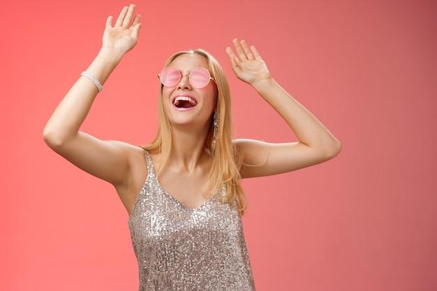 Podekscytowana, chłodna, podekscytowana młoda blond kobieta w srebrnej stylowej błyszczącej sukience okularach przeciwsłonecznych podnosi ręce do góry, bawiąc się tańcząc na parkiecie nocnym rzuć imprezę świętować urodziny, czerwone tło