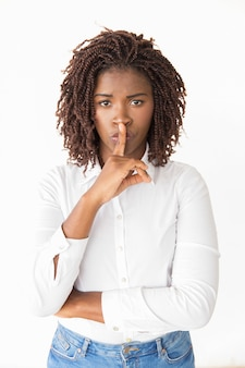 Podekscytowana cicha młoda kobieta robi gest ciszy