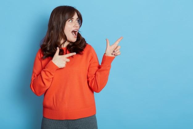 Podekscytowana Ciemnowłosa Kobieta Ubrana W Swobodny Strój, Wskazująca Na Bok Obiema Rękami, Odwracająca Wzrok Z Szeroko Otwartymi Ustami Odizolowanymi Na Niebieskiej ścianie. Premium Zdjęcia