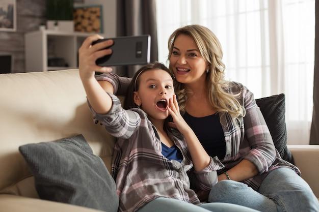 Podekscytowana córka robi selfie z matką za pomocą smartfona. szczęśliwe dziecko.