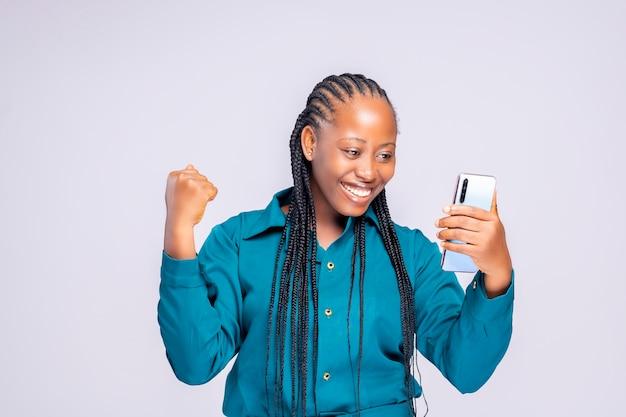 Podekscytowana czarna afrykanka używająca telefonu komórkowego na czacie z przyjaciółmi na socila media
