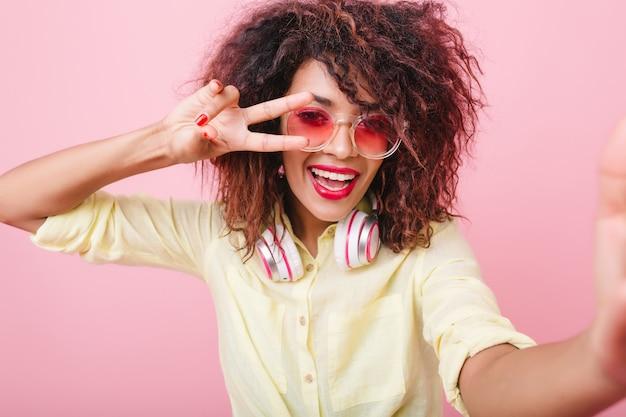 Podekscytowana czarna dziewczyna w ładny żółty strój, śmiejąc się podczas robienia selfie. kryty portret wspaniałej afrykańskiej modelki, która robi sobie zdjęcie pokazując palcami znak pokoju.
