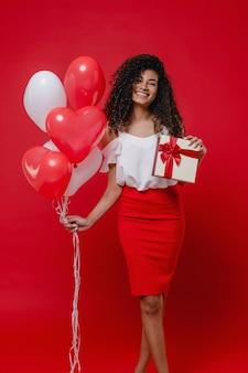 Podekscytowana czarna kobieta z kolorowymi balonami w kształcie serca i walentynkowym prezentem na czerwonej ścianie