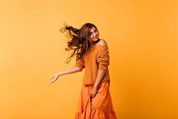 Podekscytowana długowłosa dziewczyna z ślicznym uśmiechem taniec na żółto. dobrze ubrana biała dama wyrażająca pozytywne emocje.
