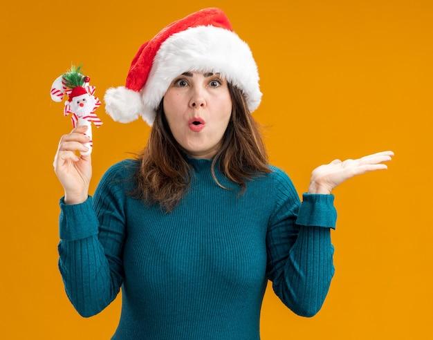 Podekscytowana dorosła kaukaska kobieta w kapeluszu santa trzyma laskę cukrową i trzyma rękę otwartą na białym tle na pomarańczowym tle z miejsca na kopię