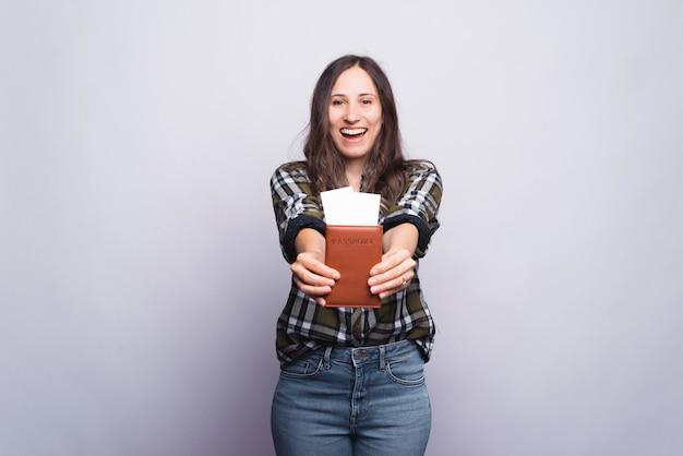 Podekscytowana dziewczyna pokazuje aparatowi jej paszport i bilety na białym tle.