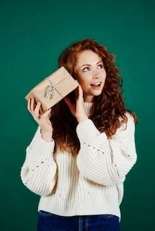 Podekscytowana dziewczyna potrząsa prezentem