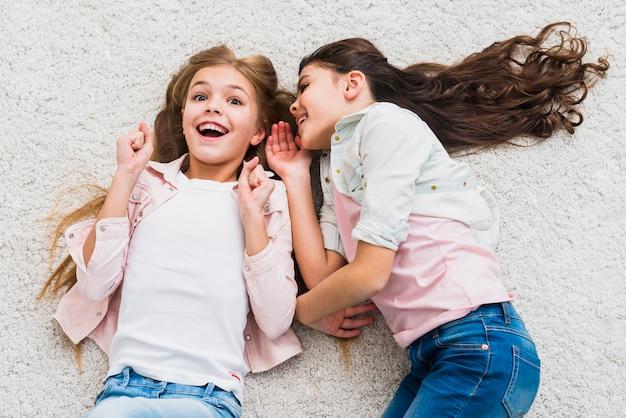 Podekscytowana dziewczyna słucha przyjaciela szepczącego do jej ucha leżącego na dywanie