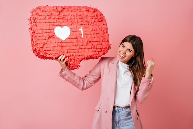 Podekscytowana dziewczyna trzyma jak ikona na różowym tle. studio strzałów z uroczą kobietą ze znakiem sieci społecznej.