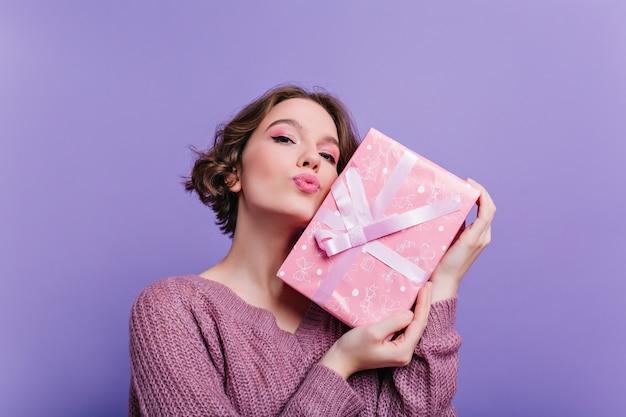 Podekscytowana dziewczyna w różowych butach tańczy na fioletowej ścianie. wewnątrz zdjęcie stylowej młodej kobiety w długiej białej spódnicy i szaliku z dzianiny, wygłupiającej się podczas sesji zdjęciowej.