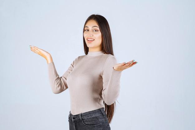 Podekscytowana dziewczyna w szarej koszuli.