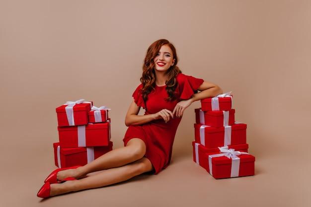 Podekscytowana dziewczyna z kręcone fryzury, pozowanie na przyjęcie urodzinowe. spektakularna kobieta w czerwonej sukience siedząca obok prezentów noworocznych.