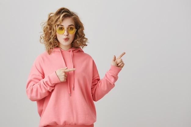 Podekscytowana dziewczyna z kręconymi włosami w okularach przeciwsłonecznych wskazująca w prawo, wskazująca drogę