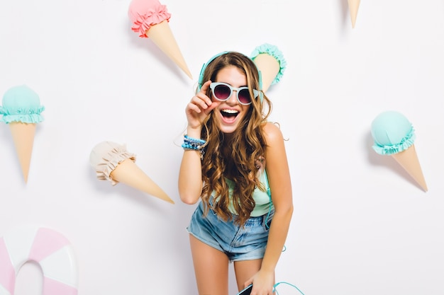 Podekscytowana dziewczyna z lśniącymi kręconymi włosami pozuje na zdobionej ścianie w dżinsowych szortach i ciemnych okularach przeciwsłonecznych. portret błogiej młodej kobiety stojącej z telefonem i słuchawkami z radosnym uśmiechem.