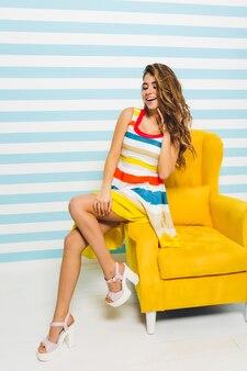 Podekscytowana dziewczyna z piękną fryzurą odwracając wzrok, siedząc na nowoczesnych żółtych meblach na ścianie w paski. portret marzycielskiej młodej kobiety w jasnej modnej sukni dotykając włosów ręką.
