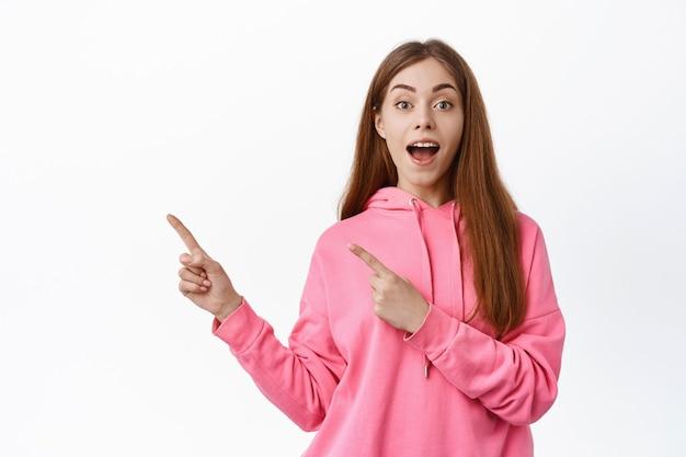 Podekscytowana dziewczyna zademonstrowała tekst promocyjny, punkty w lewo i wygląda na zdziwioną, pokazując niesamowitą ofertę reklamową, stojąc nad białą ścianą
