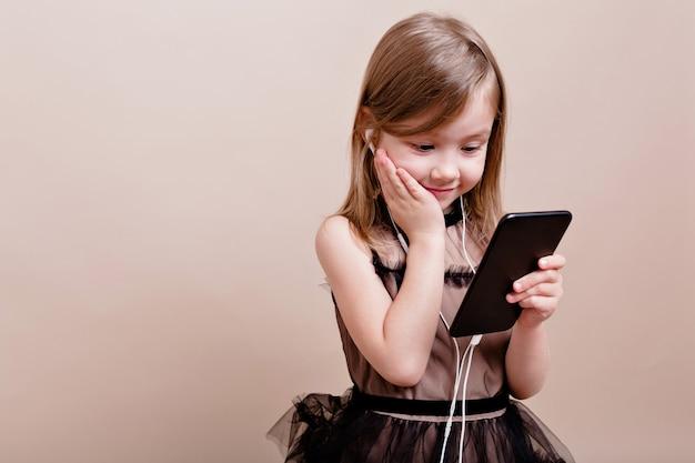 Podekscytowana dziewczynka otrzymała nowy telefon komórkowy i cieszy się nim. urocza dziewczyna z prawdziwymi emocjami trzymająca smartfon i słuchająca muzyki z wielkimi emocjami, miejsce na tekst