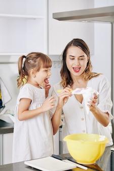 Podekscytowana dziewczynka patrzy na swoją matkę, przygotowując tort urodzinowy w domu, wypełniając torbę z bitą śmietaną