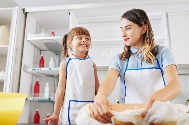 Podekscytowana dziewczynka patrzy na swoją matkę toczącą tort z bitą śmietaną i mandarynką w środku