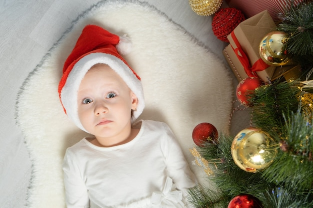 Podekscytowana dziewczynka w kapeluszu santa leżącego pod choinką. widok z góry.