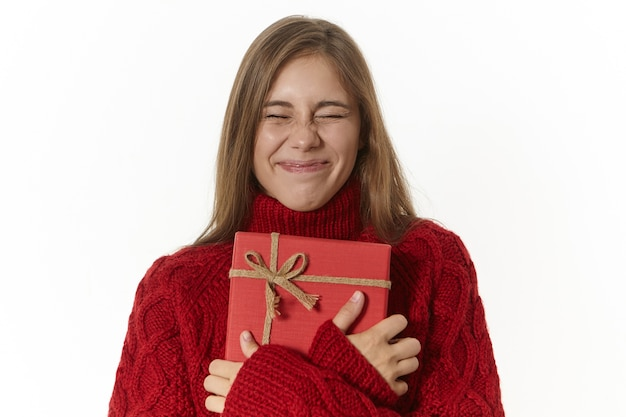 Podekscytowana ekstatyczna dziewczyna w przytulnym swetrze z dzianiny, z zamkniętymi oczami i obejmująca fantazyjne czerwone pudełko, niecierpliwie czekająca na otwarcie