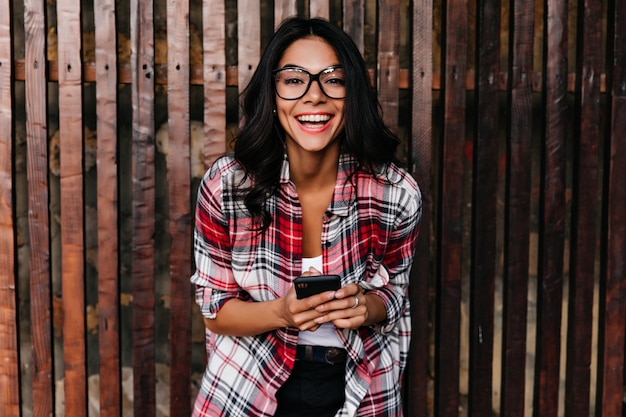 Podekscytowana elegancka dziewczyna w wiosennym stroju, śmiejąc się na drewnianej ścianie. odkryty strzał niesamowitej kobiety łacińskiej w okularach, trzymając telefon z uśmiechem.