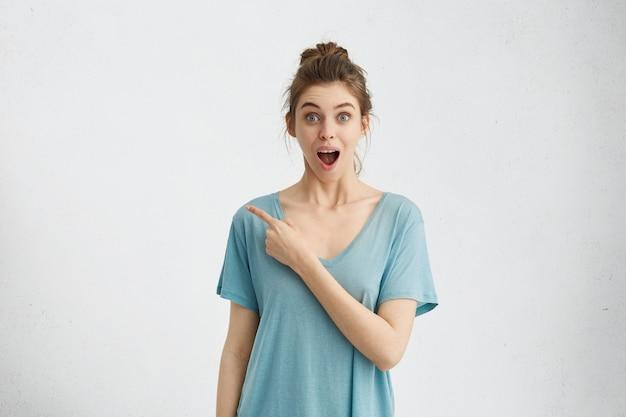 Podekscytowana, emocjonalna młoda europejska klientka szeroko otwierająca usta i wyskakująca oczy, wskazująca w bok palec wskazujący, pokazująca pustą białą ścianę
