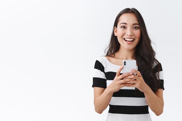 Podekscytowana, entuzjastyczna, azjatycka kobieta w swobodnym stroju, trzymająca smartfona, zachwycona uśmiechnięta i patrząca kamera, nagrywająca wideo lub fotografująca przez telefon komórkowy, białe tło