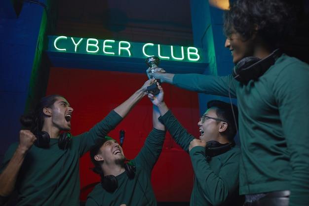 Podekscytowana grupa graczy biorących udział w konkursie gier komputerowych wspólnie zdobywają puchar