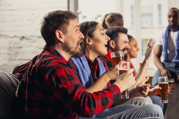 Podekscytowana grupa ludzi oglądająca mecz piłki nożnej w domu