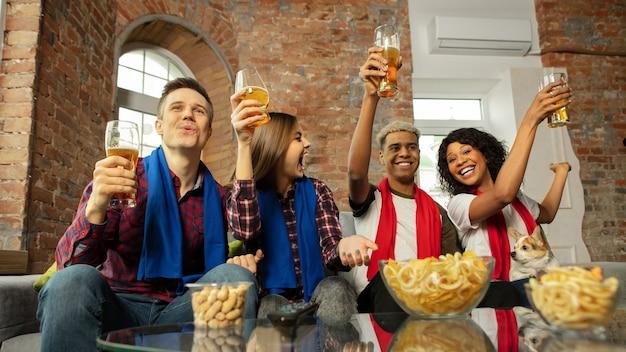Podekscytowana grupa ludzi oglądająca mecz sportowy w domu
